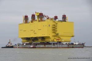 Vijf sleepboten slepen converterstation de Eemshaven in